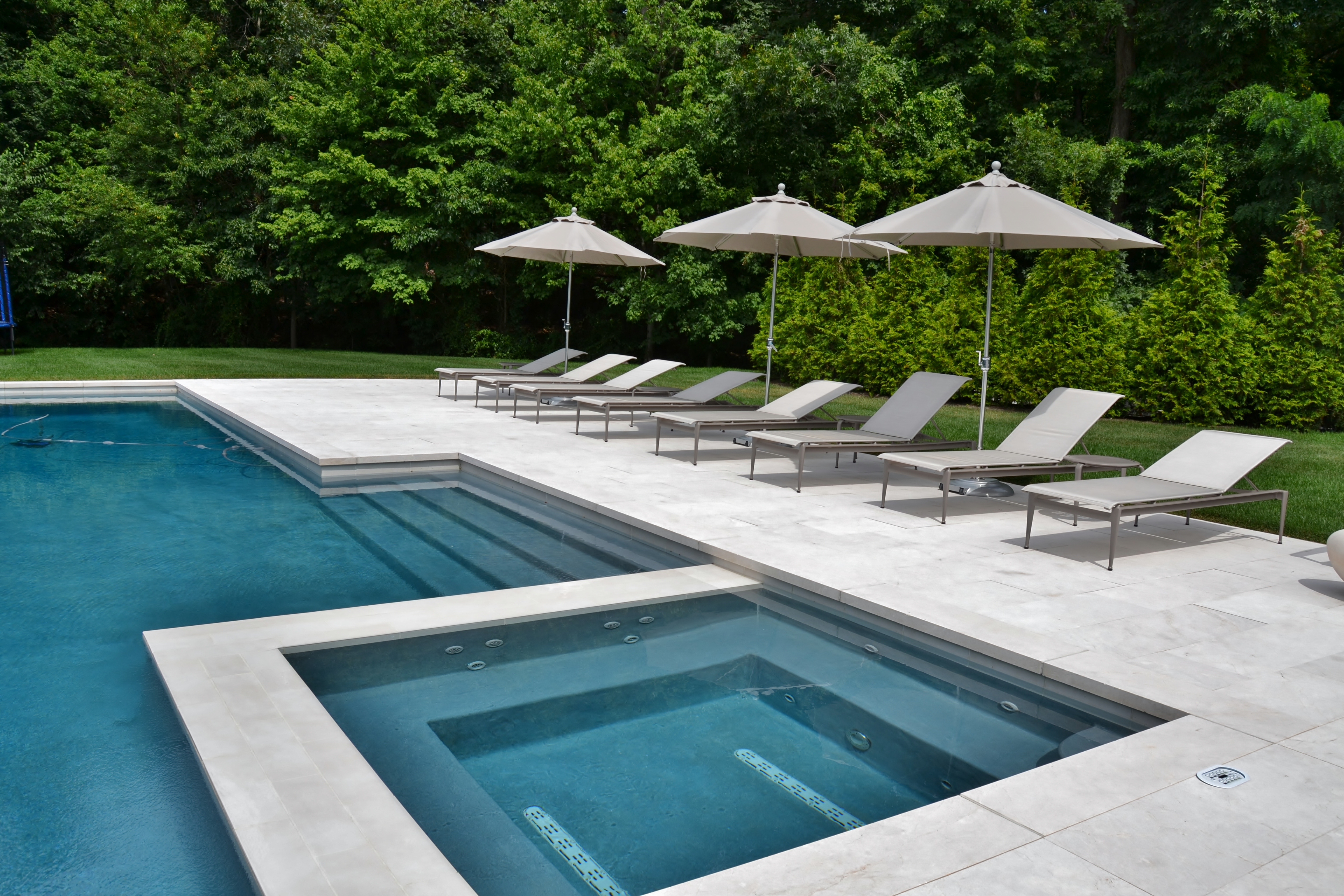 swimming pool and spa design with an elevated patio space equipped with an outdoor kitchen bar area outdoor television and fireplace this backyard is. beautiful ideas. Home Design Ideas