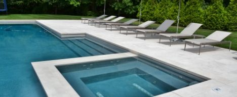Inground concrete pool with spa and lounge seating