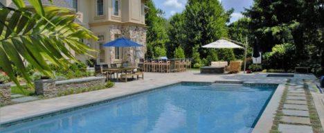 Inground pool design with stone pavers and custom patio